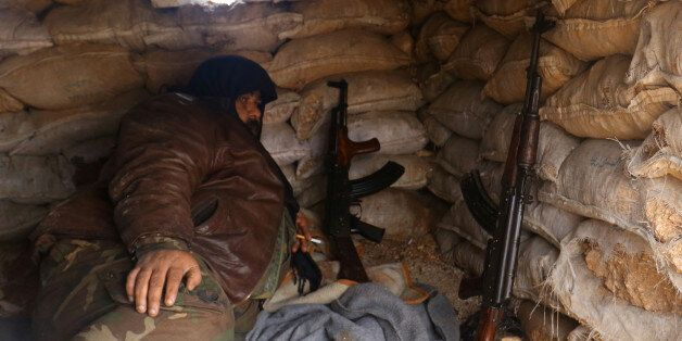 A rebel fighter rests with his weapons behind sandbags at insurgent-held al-Rashideen, Aleppo province,...