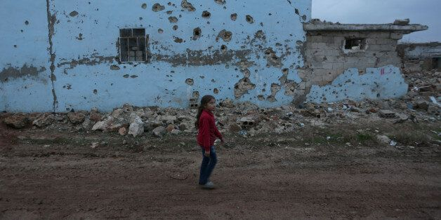 A girl walks near a damaged house in al-Rai town, northern Aleppo province, Syria December 27, 2016....