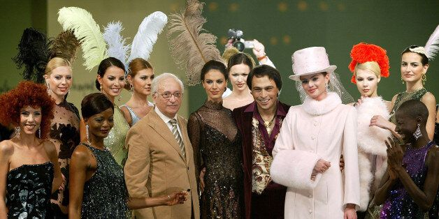Designers Yildirim Mayruk and Barbaros Sansal are flanked by models presenting creations from their 2004-2005...