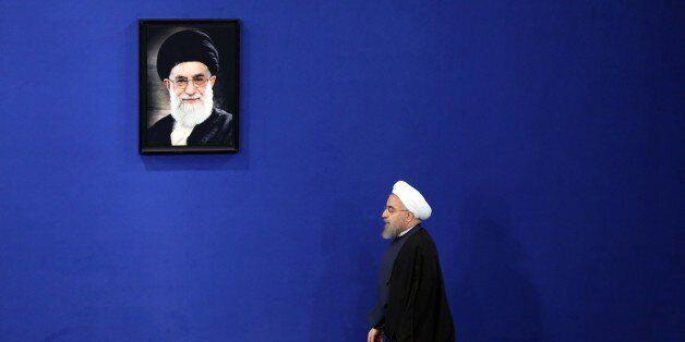 Iranian President Hassan Rouhani walks past a portrait of Iranian supreme leader Ayatollah Ali Khamenei...