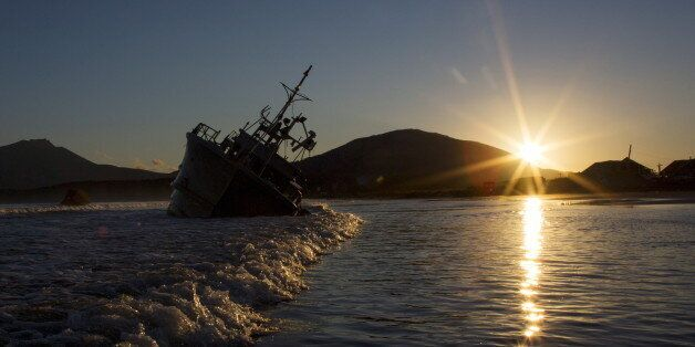 The sun sets near the rusty hulk of a ship that is stranded on the beach in Yuzhno-Kurilsk, the main...