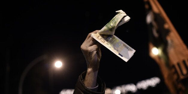 TOPSHOT - A demonstrator holds banknotes during an anti-austerity demonstration of pensioners in central...