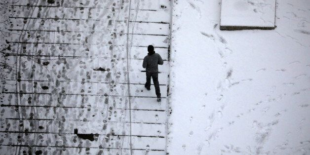A man walks amongst footsteps in the snow in Toronto, Canada December 11, 2016. REUTERS/Kevin