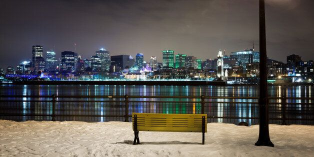A winter night in Montreal. Park bench and street light with the St Lawrence river and downtown Montreal...
