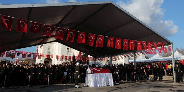 People gather behind the flag-wrapped coffin of Turkish soldier Goksel Mustafa Agacyetistiren, who was...