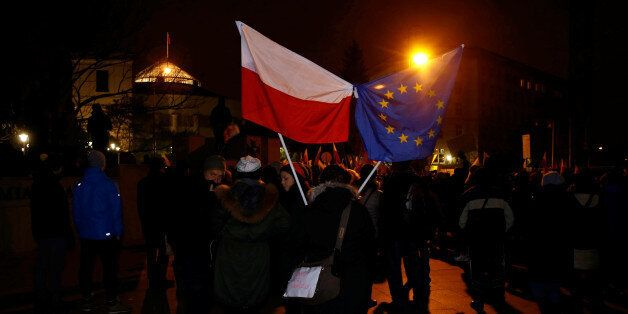 Demonstrators hold Polish and EU flags during a protest outside the Parliament building in Warsaw, Poland...
