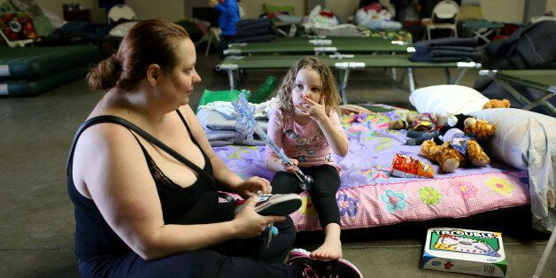 Jennifer Moss (L), of Marysville, ties her daughter Kaylin's shoes at the Salvation Army relief center...
