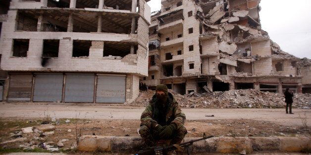 A member of forces loyal to Syria's President Bashar al-Assad sits near damaged buildings in Aleppo's...