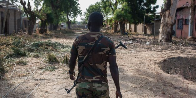A nigerian soldier patrols in the streets of Bama in northeast Nigeria on December 8, 2016.The houses...