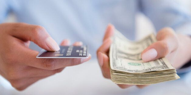 Hispanic woman holding cash and credit