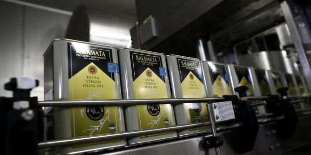 Cans of extra virgin olive oil pass along the automated production line at the bottling and processing...