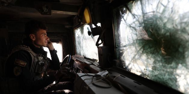 A soldier of the Iraqi Special Forces drives an armoured vehicle in the Aden district of Mosul after...