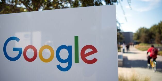 A man rides a bike passed a Google sign and logo at the Googleplex in Menlo Park, California on November...