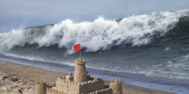 Tidal wave approaching sandcastle with