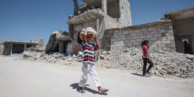 KOBANE, SYRIA - JUNE 20: (TURKEY OUT) A boy carries bread as he walks past the destroyed buildings in...