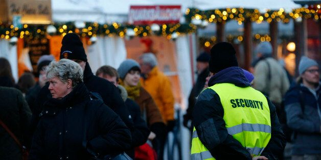 A security officer watches people visiting the Gendarmenmarkt Christmas market on the first day of its...