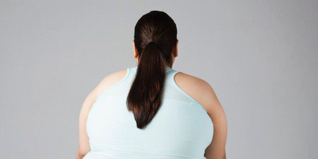 Overweight woman sitting on fitness ball, rear