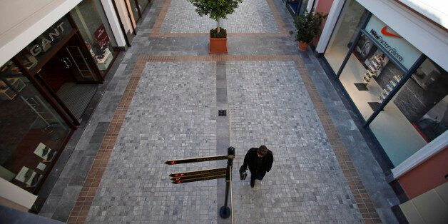 Pedestrians pass luxury goods stores in an empty arcade at the McArthurGlen designer shopping outlet...