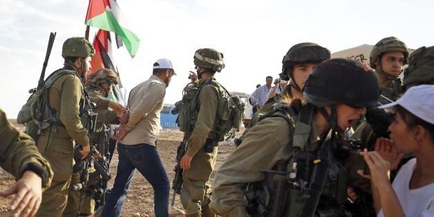 Israelis soldiers detain a Palestinian activist during a demonstration against the construction of Jewish...