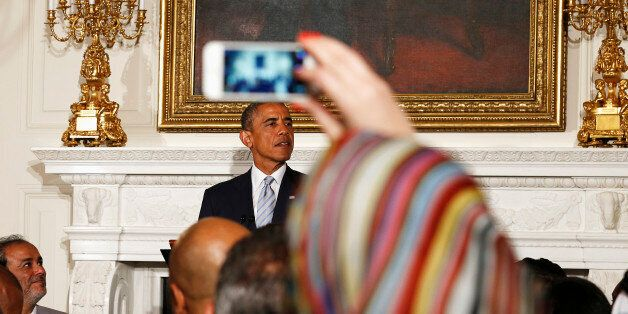A Muslim woman takes a photo as U.S. President Barack Obama speaks while hosting an Iftar dinner at the...