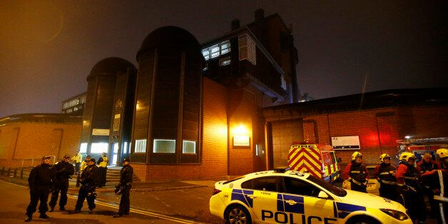 Police officers and firemen stand outside Winson Green prison, run by security firm G4S, after a serious...