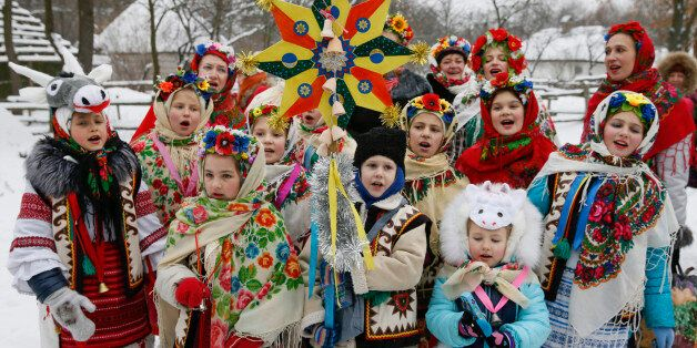 Children dressed in traditional costumes sing Christmas carols as they gather to celebrate the Orthodox...