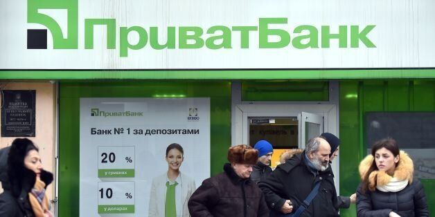 Clients walk out the office of the PrivatBank in the center of Kiev on December 19, 2016. Ukrainian President...