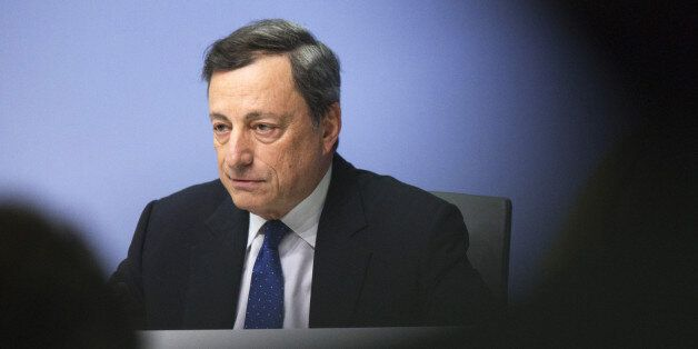Mario Draghi, president of the European Central Bank (ECB), looks on during a news conference to announce...