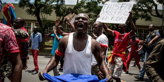 A Congolese protester holds a book of the DRC's constitution in defiance against the President of the...