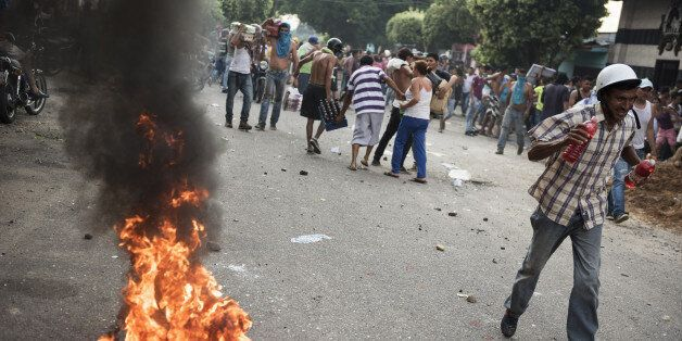People walk past a tire set on fire by demonstrators during a protest in La Fria, Tachira, Venezuela,...