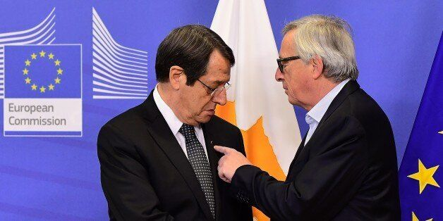 Cyprus President Nicos Anastasiades (L) is welcomed by European Commission President Jean-Claude Juncker...