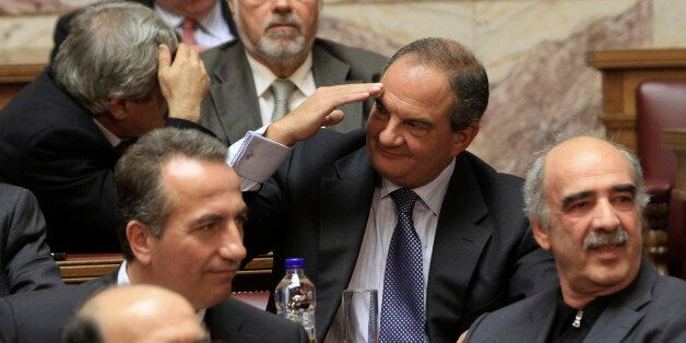 Former conservative Prime Minister Costas Karamanlis (C) greets a colleague during a New Democracy party...