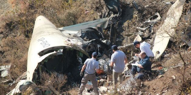 Overseas investigators examine the wreckage of a Pakistan International Airlines (PIA) passenger plane...