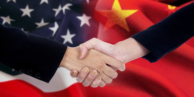 Two businesspeople handshake after good deal in front of an american and chinese