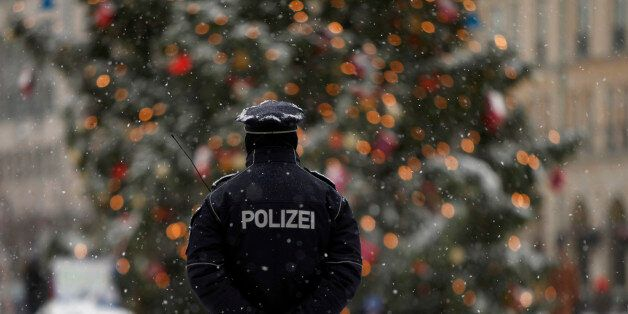 A police officer keeps watch near a Christmas tree during a snowy day in central Berlin, December 14,...