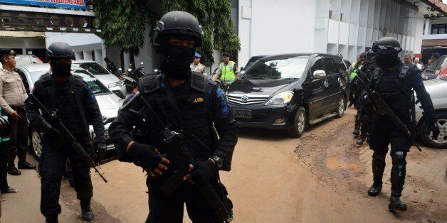 Armed Indonesian elite police commandos secure the exit at the court house for the departure of a vehicle...