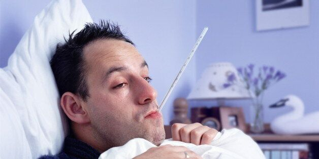 Man lying in bed, with thermometer in mouth, close-up