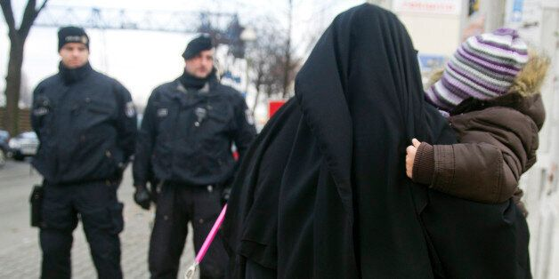 BERLIN, GERMANY - JANUARY 13: A Muslim woman, wearing a burqa, carries a child as she walks past police...