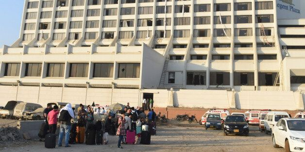 Guests are gather outside a Regent Plaza Hotel following a fire in the Pakistan's port city of Karachi...