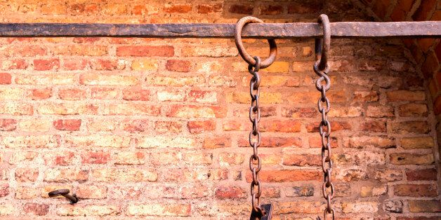 Middle aged prisoners chains and cuffs over a brick