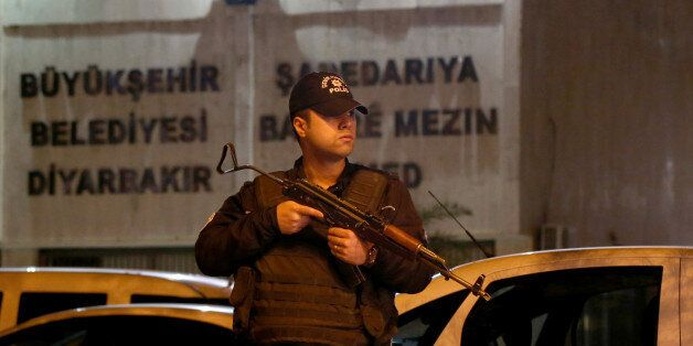 A riot policeman stands guard in front of the Metropolitan Municipality headquarters in the Kurdish-dominated...