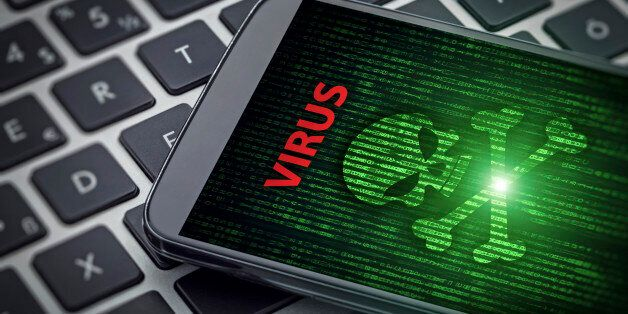 Virus alert on the screen of smartphone on laptop computer. Skull of death on data flowing background....
