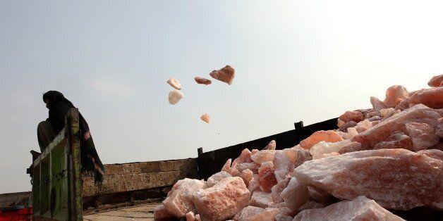 A Pakistani miner loads salt stones onto a truck at the Khewra salt mine in Khewra,some 160 kms southeast...