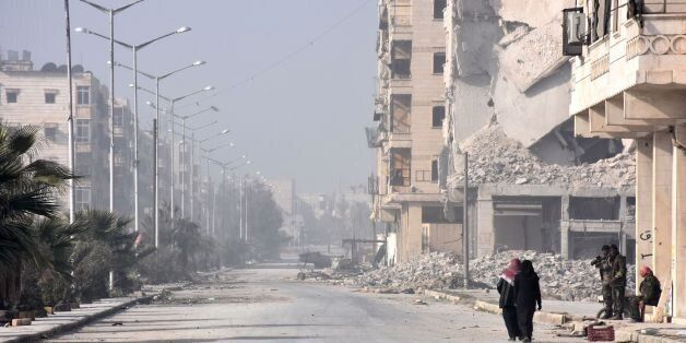 Syrian civilians arrive at a checkpoint, manned by pro-government forces, at the al-Hawoz street roundabout,...
