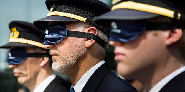 COLOGNE, GERMANY - MAY 14: Pilots and airline personnel protest wearing sleeping masks against proposed...