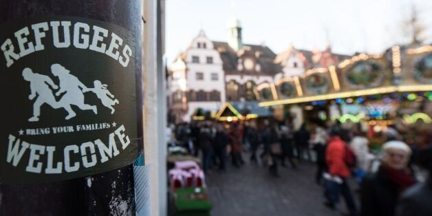 A sticker reading 'Refugees Welcome' is fixed on a pole on December 5, 2016 in Freiburg, southwestern...