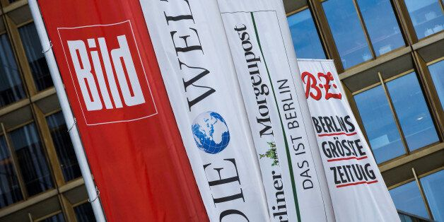 Flags with the logos of the main newspapers of German publisher Axel Springer fly outside its headquarters...