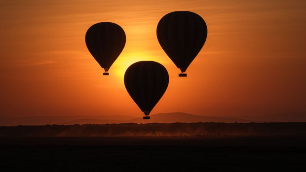 TOPSHOT - Hot-air balloons fly up with tourists at sunrise in the Masai Mara game reserve in Kenya on September 20, 2019. (Photo by Yasuyoshi CHIBA / AFP)        (Photo credit should read YASUYOSHI CHIBA/AFP/Getty Images)