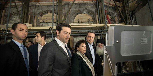 Christians pray at Jesus' tomb as a team of experts begins renovation of the structure in the Church...