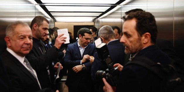 Alexis Tsipras, Greece's prime minister, centre, travels in an elevator between following a meeting at...